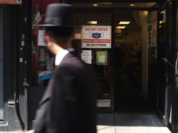 Residents walk through the Brooklyn neighborhood of Borough Park on September 23 in New York City. Borough Park is one of numerous Brooklyn neighborhoods that are witnessing a spike in the number of COVID-19 cases.