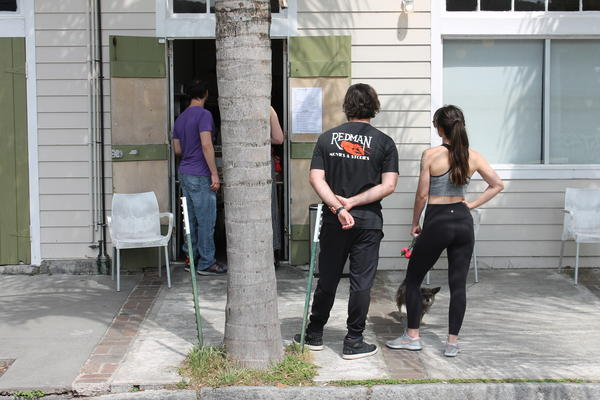 Customers wait outside a walk-up window at The Orange Couch in New Orleans. March 19, 2020.