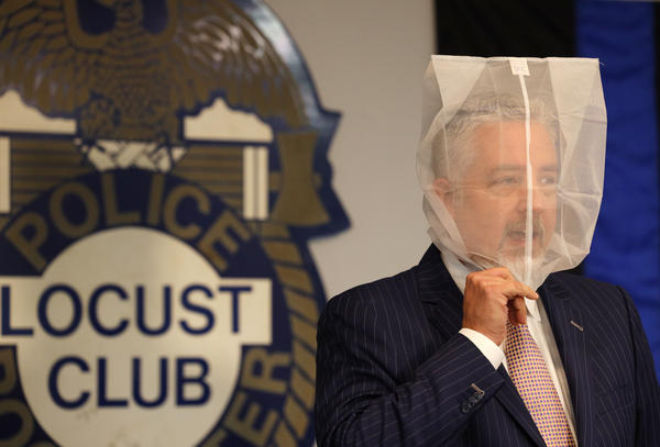 """Attorney James Nobles puts a mesh bag, also known as a """"spit sock,"""" over his head during a news conference Thursday. He said a spit sock wouldn't have obstructed Daniel Prude's breathing when officers placed one over his head in March."""