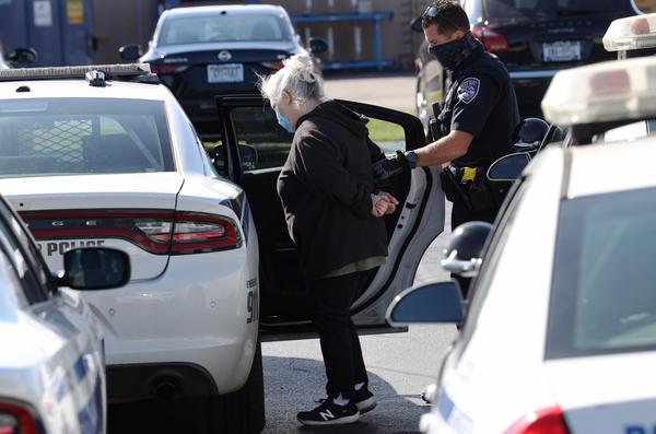 Police detain activist Mary Adams outside the Locust Club headquarters Thursday.