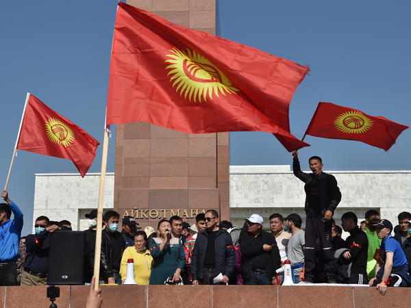 People protest beside the parliament building in Bishkek, which also houses the offices of Kyrgyzstan's president, during protests on Monday.