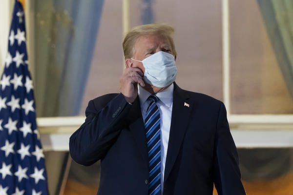 President Donald Trump removes his mask as he stands on the Blue Room Balcony upon returning to the White House Monday, Oct. 5, 2020, in Washington, after leaving Walter Reed National Military Medical Center.