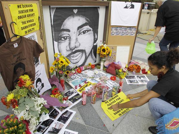 A woman leaves a sign at a street-side memorial to shooting victim Oscar Grant in Oakland, Calif., in 2010. A Northern California prosecutor announced Monday that she will reopen the investigation into the killing of Grant at a train station by a police officer 11 years ago.