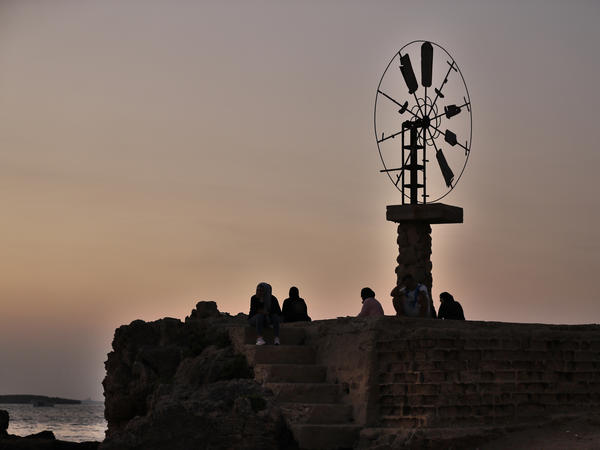 Relatives of Mohammed Khaldoun sit next to a windmill in Tripoli, Lebanon, as they pray for his safe return home last month. Khaldoun, 27, was missing at sea after he tried to reach Cyprus on an overcrowded boat.