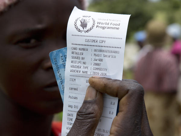 A woman holds a voucher before receiving food aid in Mudzi, Zimbabwe, in February. On Friday, the United Nations World Food Programme received the 2020 Nobel Peace Prize.
