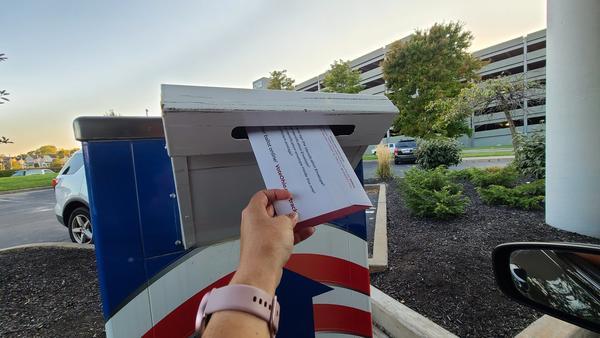voter dropping ballot into drop box