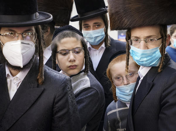 Members of the Orthodox Jewish community gather around a journalist as he conducts an interview on a street corner, last Wednesday, in the Borough Park neighborhood of the Brooklyn borough of New York. Gov. Andrew Cuomo moved to reinstate restrictions on businesses, houses of worship and schools in and near areas where coronavirus cases are spiking.