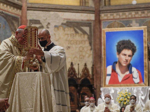 Cardinal Agostino Vallini, left, holds a relic of Carlo Acutis, an Italian boy who died in 2006 of leukemia at the age of 15. Acutis was beatified during a Mass celebrated in the Basilica of St. Francis of Assisi in Assisi, Italy, on Saturday.