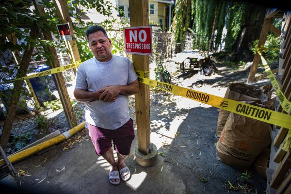 Amid caution tape and no trespassing signs, Marvin Moreno stands outside the apartment where he lived in East Boston. His landlord pressured him to leave, despite the eviction moratorium. (Jesse Costa/WBUR)
