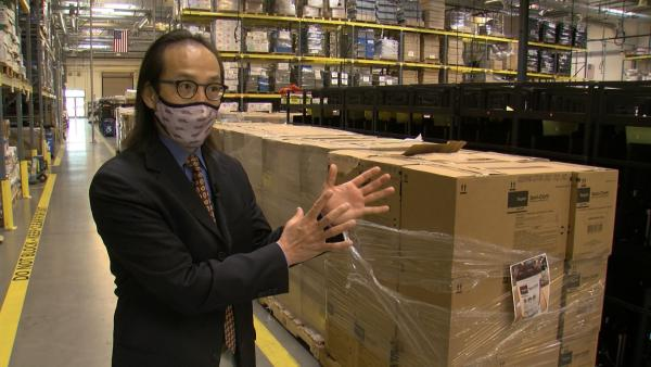 San Diego County Registrar of Voters Michael Vu stands in a warehouse filled with supplies for the 2020 election.
