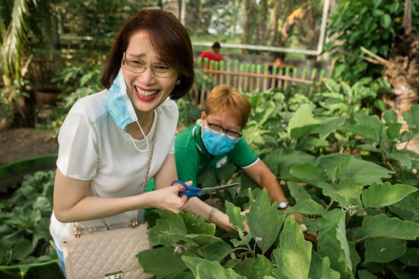 """Geraldine Roman, the first openly transgender person to be elected to the Philippine Congress, visits a vegetable garden in Bataan. She leads a program called Oh My Gulay — <em>gulay</em> is Tagalog for """"vegetables."""" It encourages people to grow vegetables to eat and sell and is aimed especially at those who have lost income as a result of the pandemic."""