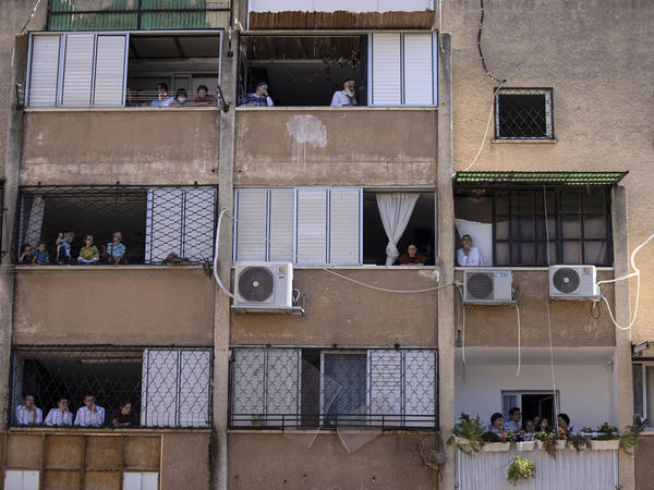 Ultra-Orthodox Jews watch a funeral for Rabbi Mordechai Leifer from their balconies in the port city of Ashdod, Israel, on Oct. 5. The rabbi, who had been the spiritual leader of a small ultra-Orthodox community founded a century ago in Pittsburgh, died after being infected with COVID-19.