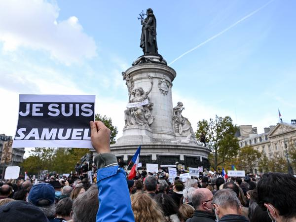 "A demonstrator carries an ""I am Samuel"" sign as people gather Sunday in Place de la République in Paris to pay tribute to slain history teacher Samuel Paty. Similar rallies took place in other French cities as the country reels from the attack."