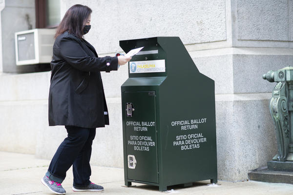 A voter casts her early-voting ballot at a drop box outside City Hall in Philadelphia on Oct. 17.
