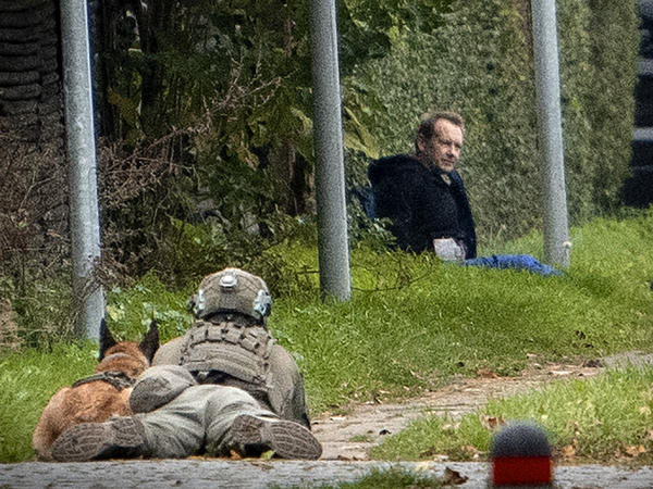 A police marksman and his dog observes convicted killer Peter Madsen threatening police with detonating a bomb while attempting to break out of jail Tuesday in Albertslund, Denmark.