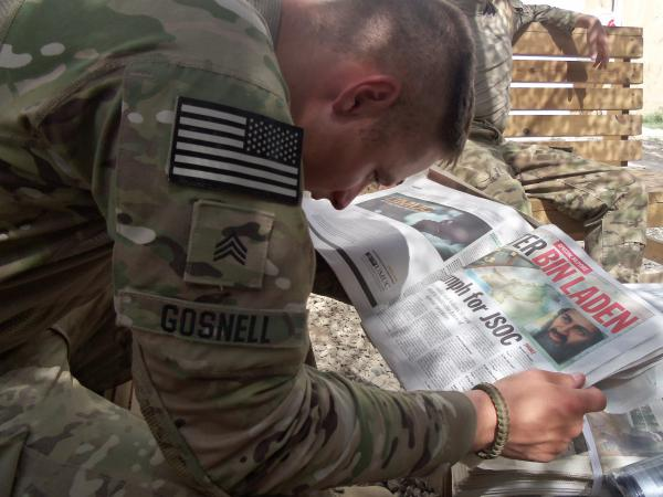 A soldier in Logar Province, Afghanistan reads about the capture of Osama Bin Laden in a 2011 issue of the Stars and Stripes.