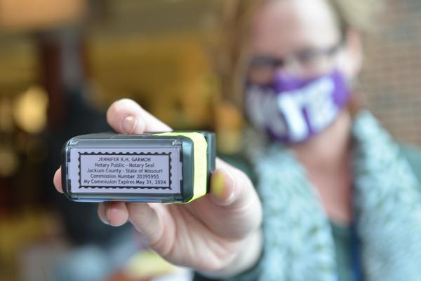 Jenny Garmon, a legal and government information specialist with the Kansas City Library and a notary public, displays the stamp she uses to notarize voters who bring mail-in ballots. She was at the Kansas City Health Department on Tuesday, where she regularly helps voters get registered.