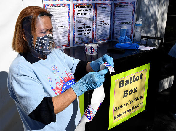 "Volunteer Esmeralda Raymond gets a roll of ""I Voted"" stickers ready at a polling site in Las Vegas on the first day of in-person early voting on Oct. 17."