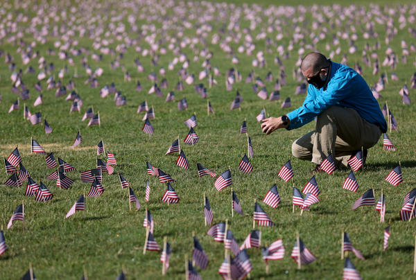 Chris Duncan, whose 75 year old mother Constance died from COVID on her birthday, photographs a COVID Memorial Project installation of 20,000 American flags on the National Mall as the United States crosses the 200,000 lives lost in the COVID-19 pandemic. (White House. (Photo by Win McNamee/Getty Images)