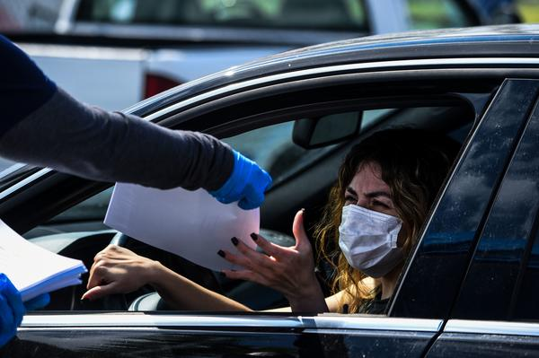 A woman collects unemployment forms at a drive through collection point outside John F. Kennedy Library in Hialeah, Florida, on April 8, 2020. (CHANDAN KHANNA/AFP via Getty Images)