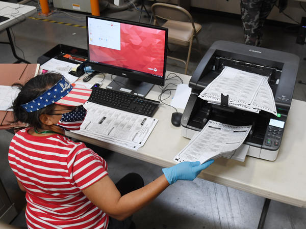 A Clark County, Nev., election worker scans mail-in ballots earlier this week in North Las Vegas. The state allows officials to count ballots received in advance of Election Day in order to speed the tabulation of results that evening.