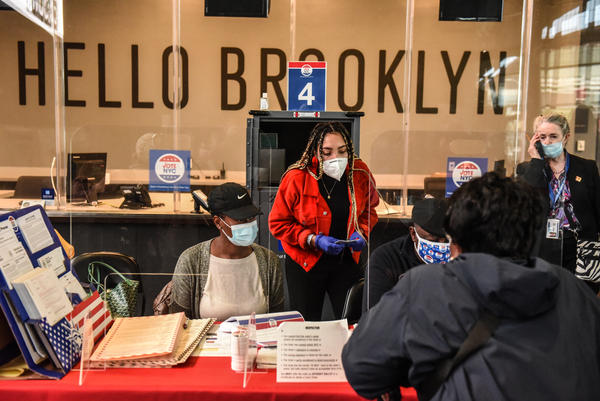 Poll workers check in a voter Oct. 24 at the Barclays Center in New York City.