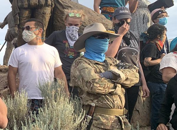 Bryce Provance, in a blue face covering, stands with his back to a statue of Juan de Oñate on June 15 in Albuquerque. The Civil Guard's presence there escalated tensions before a protestor was shot.
