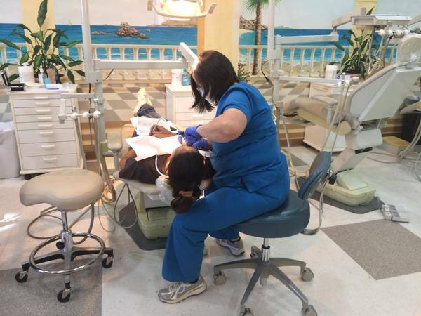 A hygienist numbs a patient in preparation for a tooth extraction at Smiles of Hope .