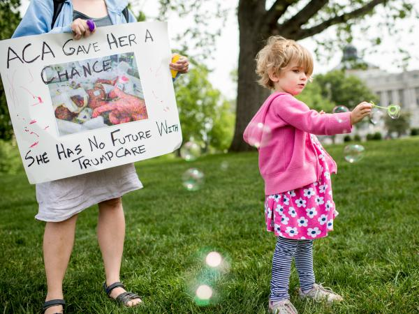 Charlie Wood of Charlottesville, Va., plays with bubbles during a May 4, 2017, rally near the Capitol to oppose proposed changes to the Affordable Care Act. Charlie was born a few months prematurely, and her mother, Rebecca (left), fears changes to the health law will negatively affect her care.