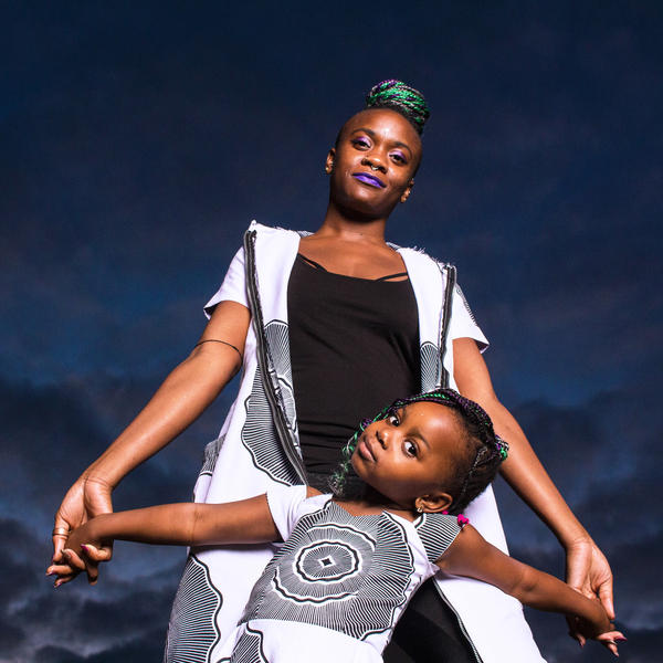 """Tobi, pictured with their daughter Gabrielle, is a nonbinary Yoruba Nigerian who lives in the United Kingdom. Tobi identifies as queer, bisexual and femme. They say they have to change the way they present when they visit Nigeria to avoid conflict with family members they're not fully out to. But Tobi finds peace in """"living in their truth"""" as much as possible."""