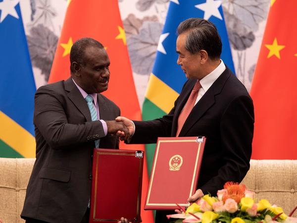 China's Foreign Minister Wang Yi shakes hands with Solomon Islands' Foreign Minister Jeremiah Manele after the signing of a joint communique in Beijing establishing diplomatic relations between China and the Solomon Islands.