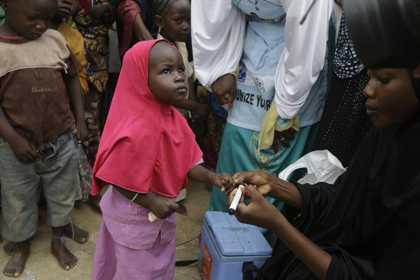 Photo taken Sun., Aug. 28, 2016. A health official inks a child finger to indicate she has been administered with a polio vaccine at a camp of people displaced by Islamist extremist in Maiduguri, Nigeria.