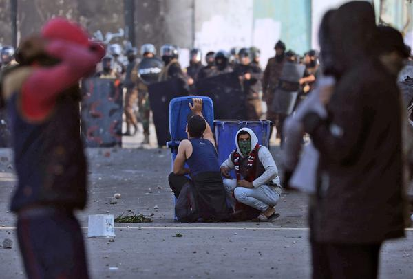 Iraqi demonstrators take cover from security forces behind trash cans during clashes in the city of Karbala on Thursday.