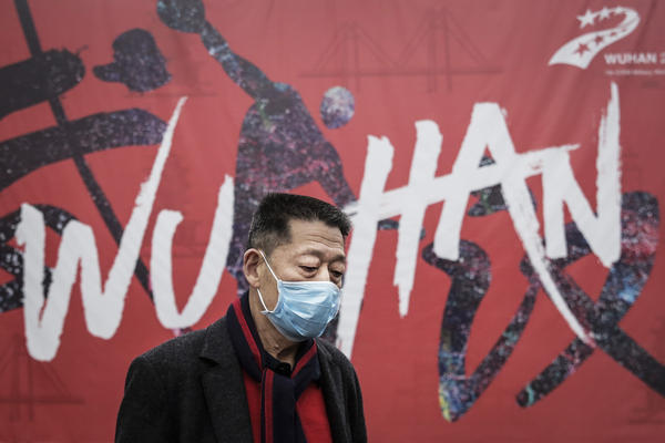A man in Wuhan, China, the epicenter of the current coronavirus outbreak, walks by a local mural.
