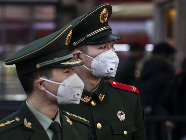 Chinese police officers wear protective masks at Beijing Station on Jan. 22. The first death outside of China from the fast-spreading coronavirus was reported Sunday in the Philippines.
