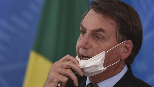 Brazil's President Jair Bolsonaro removes his mask to speak to journalists after a press conference on the coronavirus on Wednesday.