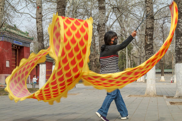 A woman dances while waving a silk ribbon with patterns that mimic dragon scales. At this park in Beijing and most other public places in China, people are still required to wear face masks.