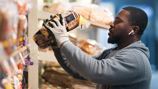 A grocery store worker stocks bread at a MOM's Organic Market in Washington, D.C., on April 2. Last week, bread sales jumped 30% compared to a year ago. But yeast sales were up more than 450%.
