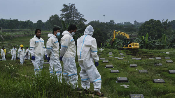 A new section of a municipal cemetery in Jakarta is expanded for graves of those suspected of dying from COVID-19.