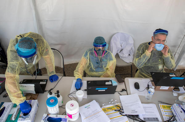 A COVID-19 testing operation stays busy in Boyle Heights, Calif. Daily case counts overall may be on the low side because access to testing is limited in some parts of the world.