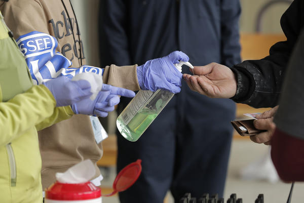 A patient arrives to pick up medication for opioid addiction and is given hand sanitizer at a clinic in Olympia, Wash. The pandemic is changing the distribution networks and supplies of street drugs across the United States, authorities say.