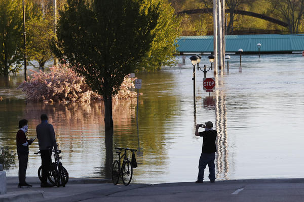 People photograph the floodwaters of the Tittabawassee River that encroached on downtown Midland, Mich., on Wednesday. Floodwaters have overtaken dams and forced the evacuation of about 10,000 people from communities in central Michigan.