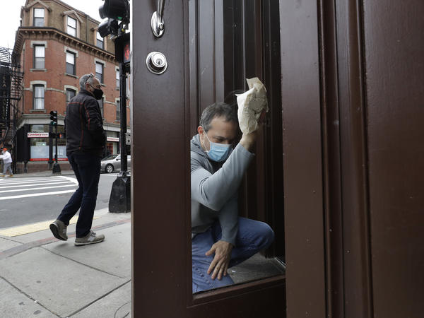 Manager Mike Bonavita wears a protective mask as he cleans windows at the Quattro Italian restaurant in Boston on May 12 during the coronavirus pandemic. This month, Massachusetts' governor declared wearing masks mandatory.