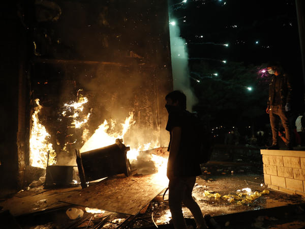 Protesters set fires at the 3rd Precinct of the Minneapolis Police Department on Thursday. Protests over the death of George Floyd, the black man who died in police custody, continued in Minneapolis for a third straight night.