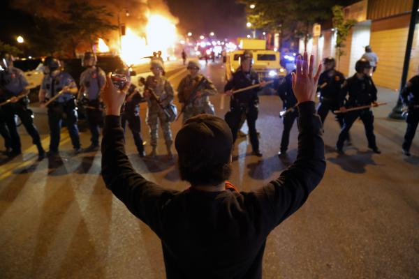A man raises his hands as police line up across the street during protests Friday in Minneapolis. Demonstrators expressed outrage and grief across the nation over the death of George Floyd, a black man who was killed by police.