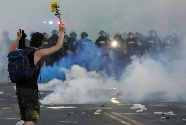 Police move towards a protester after curfew Saturday, May 30, 2020, in Minneapolis.