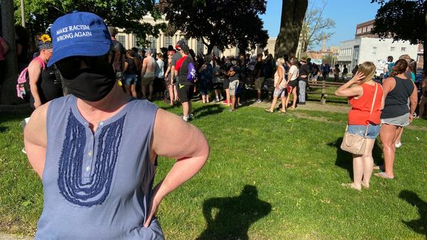 """Wearing a mask to protect herself from the coronavirus and a hat that reads """"Make Racism Wrong Again,"""" Lydia Spottswood joins a protest in Kenosha, Wis., in response to George Floyd's killing by police. She thinks people are tired of President Trump's """"meanness."""""""