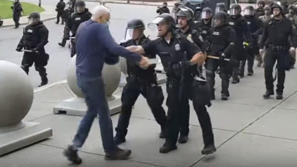 A video shows officers appearing to shove an older man who walked up to riot police Thursday in Buffalo, N.Y. Prosecutors have now filed charges against two officers.