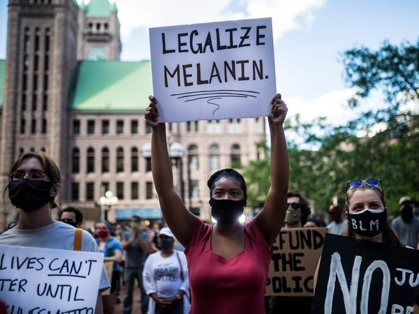 Protesters hold signs outside the Hennepin county Government Center in Minneapolis, Minn., on Thursday.