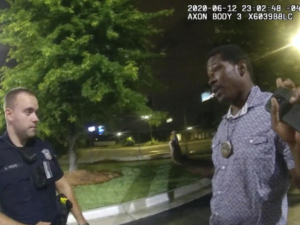 In a screenshot from body camera video provided by the Atlanta Police Department, Rayshard Brooks speaks with Officer Garrett Rolfe in a Wendy's parking lot.
